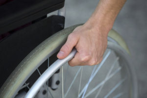 Photo of a man in wheelchair holding wheel