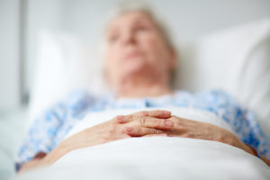 Close-up of hands of senior woman lying in hospital ward